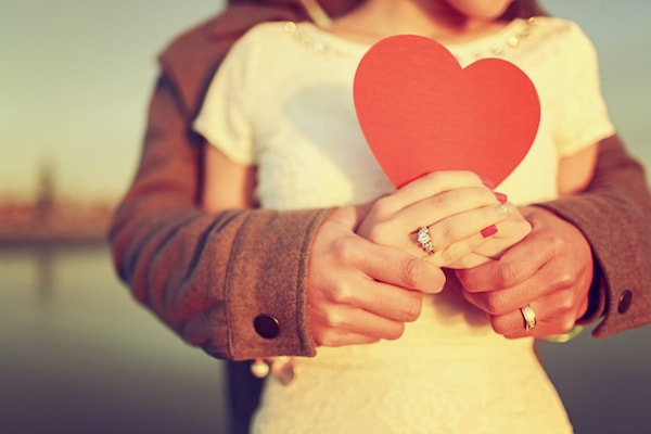 couple embracing and holding a red paper heart