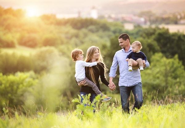 parents carrying their children through a field