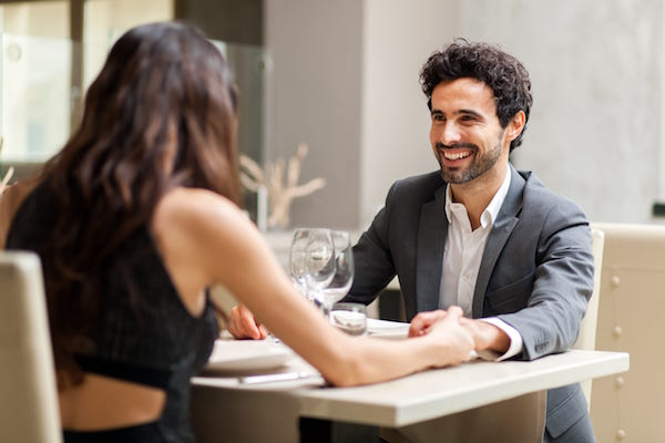 Man and woman on a date, holding hands in a restaurant