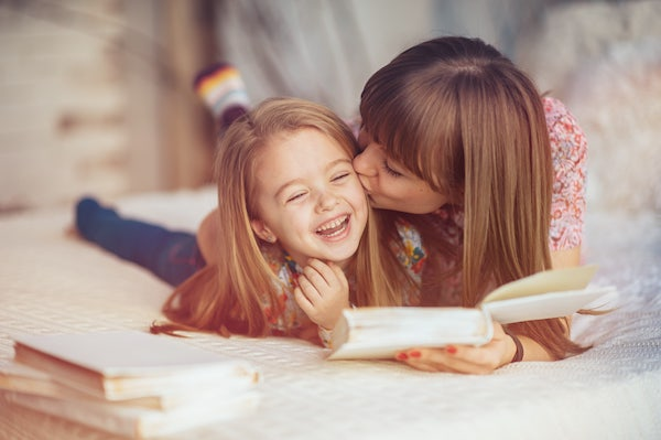 Mother kissing daughter while they read a bed time story