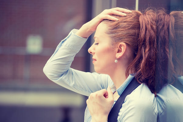 woman holding her head in distress